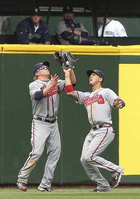 SEATTLE - JUNE 29:  Center fielder Jordan Schafer #1 (R) of the Atlanta Braves makes a catch in front of left fielder Nate McLouth #13 on a deep fly ball by Josh Bard #3 of the Seattle Mariners at Safeco Field on June 29, 2011 in Seattle, Washington. The