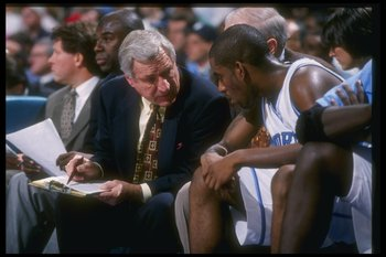 7 Dec 1996:  North Carolina Tar Heels head coach Dean Smith confers with guard Ed Cota during the Pepsi Challenge against the South Carolina Gamecocks at the Coliseum in Charlotte, North Carolina.  UNC won the game, 86-75. Mandatory Credit: Craig Jones  /
