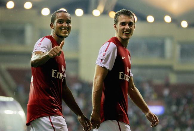 HANGZHOU, CHINA - JULY 16:  Theo Walcott (L) and Aaron Ramsey of Arsenal gestures to the fans after the pre-season friendly match between Hangzhou Greentown and Arsenal at Yiwu Meihu Stadium on July 16, 2011 in Hangzhou, China. (Photo by Lintao Zhang/Gett