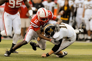 LINCOLN, NE - OCTOBER 30: Safety Courtney Osborne #12 of the Nebraska Cornhuskers hits  quarterback Blaine Gabbert #11 of the Missouri Tigers during second half action of their game at Memorial Stadium on October 30, 2010 in Lincoln, Nebraska. Nebraska De