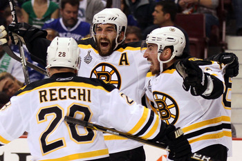 VANCOUVER, BC - JUNE 15:  Patrice Bergeron #37 of the Boston Bruins celebrates with his teammates Mark Recchi #28 and Brad Marchand #63 after scoring a goal in the first period against Roberto Luongo #1 of the Vancouver Canucks during Game Seven of the 20
