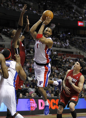 AUBURN HILLS, MI - MARCH 23:  Tracy McGrady #1 of the Detroit Pistons looks for an open teammate between Mike Bibby #0 and Dwyane Wade #3 of the Miami Heat at The Palace of Auburn Hills on March 23, 2011 in Auburn Hills, Michigan. Miami won the game 100-9