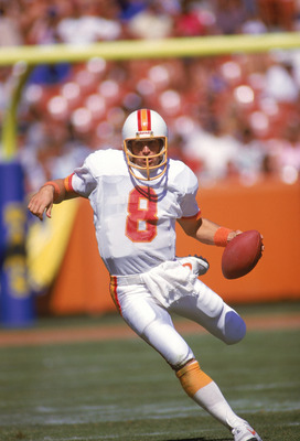 ANAHEIM, CA - OCTOBER 5:  Quarterback Steve Young #8 of the Tampa Bay Buccaneers scrambles against the Los Angeles Rams at Anaheim Stadium on October 5, 1986 in Anaheim, California. The Rams won in overtime 26-20. (Photo by Rick Stewart/Getty Images)