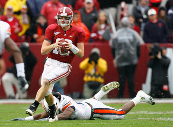 TUSCALOOSA, AL - NOVEMBER 26:  Quarterback Greg McElroy #12 of the Alabama Crimson Tide breaks away from Eltoro Freeman #21 of the Auburn Tigers at Bryant-Denny Stadium on November 26, 2010 in Tuscaloosa, Alabama.  (Photo by Kevin C. Cox/Getty Images)