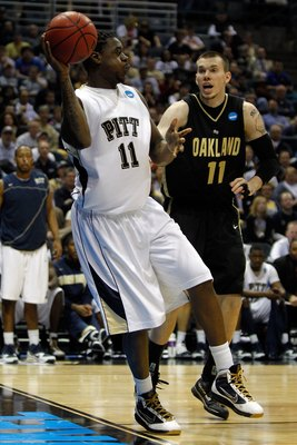 MILWAUKEE - MARCH 19:  Dante Taylor #11 of the Pittsburgh Panthers saves the ball as Will Hudson #11 of the Oakland Golden Grizzlies looks on during the first round of the 2010 NCAA men's basketball tournament at the Bradley Center on March 19, 2010 in Mi