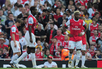 LONDON, ENGLAND - APRIL 17:  (L_R) Dejected Andrey Arshavin, Johan Djourou and Alex Song of Arsenal after referee Andre Marriner awards Liverpool a penalty kick and they equalise during the Barclays Premier League match between Arsenal and Liverpool at th