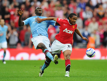 LONDON, ENGLAND - APRIL 16:  Mario Balotelli of Manchester City and Anderson of Manchester United fight for the ball during the FA Cup sponsored by E.ON semi final match between Manchester City and Manchester United at Wembley Stadium on April 16, 2011 in