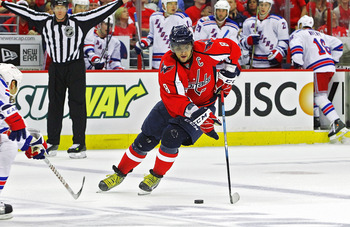 WASHINGTON, DC - APRIL 23:  Alex Ovechkin #8 of the Washington Capitals carries the puck across the blue line against the New York Rangers in Game Five of the Eastern Conference Quarterfinals during the 2011 NHL Stanley Cup Playoffs at the Verizon Center