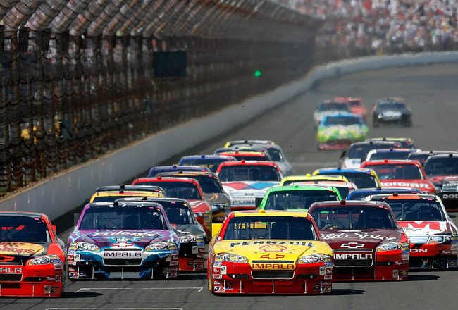 INDIANAPOLIS - JULY 25:  Jamie McMurray, driver of the #1 Bass Pro Shops/Tracker Boats Chevrolet, and Kevin Harvick, driver of the #29 Shell/Pennzoil Chevrolet, lead the pack after the final re-start during the NASCAR Sprint Cup Series Brickyard 400 at In
