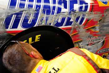 INDIANAPOLIS - JULY 26:  A crew member for the #18 Snickers Toyota driven by Kyle Busch works on the car in the garage during the NASCAR Sprint Cup Series Allstate 400 at the Brickyard at Indianapolis Motor Speedway on July 26, 2009 in Indianapolis, India