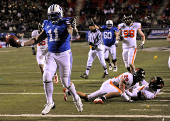 LAS VEGAS - DECEMBER 22:  Manase Tonga #11 of the Brigham Young University Cougars scores a touchdown in the fourth quarter after getting by defenders including Suaesi Tuimaunei #28 and Anthony Watkins #47 of the Oregon State Beavers during the MAACO Las