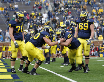 ANN ARBOR, MI - APRIL 16: David Molk #50 and Rocko Khoury #60 of the Michigan Wolverines run through the pre-game drills during the annual Spring Game at Michigan Stadium on April 16, 2011 in Ann Arbor, Michigan.  (Photo by Leon Halip/Getty Images)