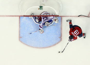 WASHINGTON, DC - APRIL 15:  Henrik Lundqvist #30 of the New York Rangers stops Nicklas Backstrom #19 of the Washington Capitals in the third period in Game Two of the Eastern Conference Quarterfinals during the 2011 NHL Stanley Cup Playoffs at Verizon Cen