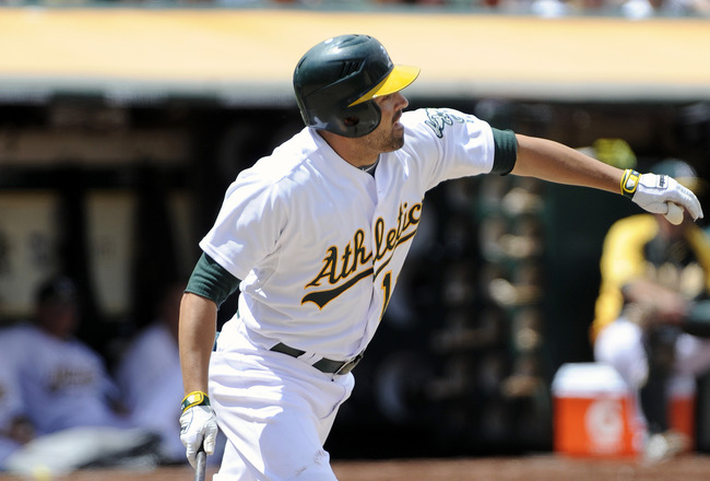 OAKLAND, CA - JULY 16: David DeJesus #12 of the Oakland Athletics gets a base hit against the Los Angeles Angels of Anaheim in the fifth inning during an MLB baseball game at the O. co Coliseum July 16, 2011 in Oakland, California. (Photo by Thearon W. He