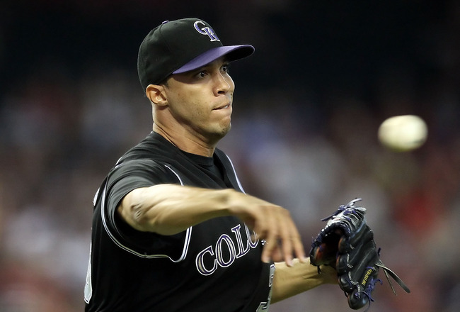 PHOENIX, AZ - JULY 24:  Starting pitcher Ubaldo Jimenez #38 of the Colorado Rockies fields a ground ball out against the Arizona Diamondbacks during the Major League Baseball game at Chase Field on July 24, 2011 in Phoenix, Arizona.  (Photo by Christian P