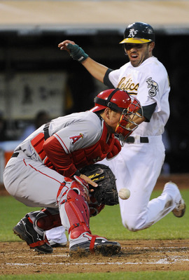 OAKLAND, CA - JULY 15: David DeJesus #12 of the Oakland Athletics slides in safe at home on an RBI double by teammate Conor Jackson #28 as Jeff Mathis #5 of the Los Angeles Angels misses the throw in the fourth inning during an MLB baseball game at the O.