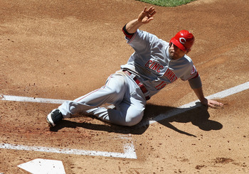 PHOENIX, AZ - APRIL 10:  Joey Votto #19 of the Cincinnati Reds slides in to score a first inning run against the Arizona Diamondbacks during the Major League Baseball game at Chase Field on April 10, 2011 in Phoenix, Arizona.  (Photo by Christian Petersen