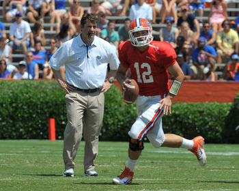 GAINESVILLE, FL - APRIL 9:  Quarterback John Brantley #12 of the Florida Gators runs from the pocket in front of coach Will Muschamp during the Orange and Blue spring football game April 9, 2011 at Ben Hill Griffin Stadium in Gainesville, Florida.  (Photo