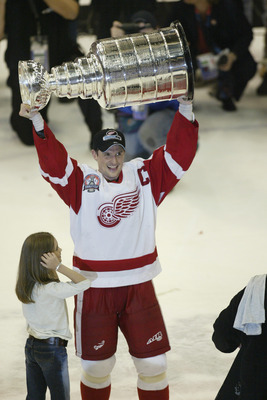 DETROIT, MI - JUNE 13:  Captain Steve Yzerman #19 of the Detroit Red Wings with his daughter Isabella raises the Stanley Cup after defeating the Carolina Hurricanes in game five of the NHL Stanley Cup Finals  on June 13, 2002 at the Joe Louis Arena in Det