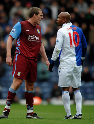 BLACKBURN, ENGLAND - NOVEMBER 21:  El Hadji Diouf of Blackburn Rovers and Richard Dunne of Aston Villa exchange views during the Barclays Premier League match between Blackburn Rovers and Aston Villa at Ewood Park on November 21, 2010 in Blackburn, Englan
