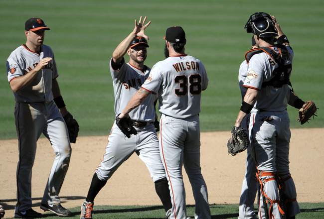 SAN DIEGO, CA - JULY 17: Brian Wilson #38 of the San Francisco Giants, left, is congratulated by teammates after the final out during the 11th inning of a baseball game against the San Diego Padres at Petco Park on July 17, 2011 in San Diego, California.