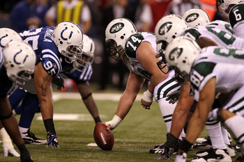 INDIANAPOLIS, IN - JANUARY 08:  Center Nick Mangold #74 of the New York Jets readies the ball for the snap against Fili Moalo #95 of the Indianapolis Colts during their 2011 AFC wild card playoff game at Lucas Oil Stadium on January 8, 2011 in Indianapoli