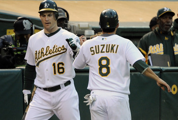 OAKLAND, CA - JULY 15: Kurt Suzuki #8 of the Oakland Athletics celebrates with teammate Josh Willingham #16 after scoring against the Los Angeles Angels in the third inning during an MLB baseball game at the O.co Coliseum July 15, 2011 in Oakland, Califor