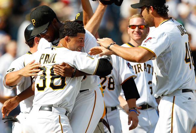 PITTSBURGH - JULY 24:  Xavier Paul #38 of the Pittsburgh Pirates is congratulated by teammates James McDonald #53 and Garrett Jones #46 after scoring the game winning run in the 10th inning against the St Louis Cardinals during the game on July 24, 2011 a