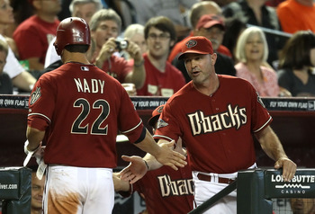 PHOENIX, AZ - JULY 24:  Manager Kirk Gibson of the Arizona Diamondbacks high fives Xavier Nady #22 after he scored a run against the Colorado Rockies during the sixth inning of the Major League Baseball game at Chase Field on July 24, 2011 in Phoenix, Ari