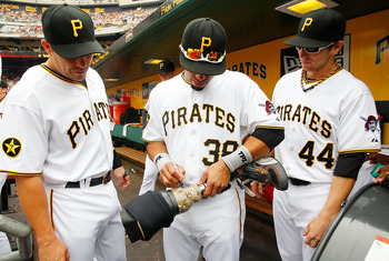 PITTSBURGH - JULY 24:  Steve Pearce #51, Xavier Paul #38, and Alex Presley #44 of the Pittsburgh Pirates sign the prosthetic leg of Afghanistan war veteran, Courtney Rauch, 24, of Perry County, Pennsylvania before the game against the St Louis Cardinals o