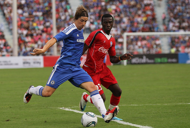 BANGKOK, THAILAND - JULY 24:  Fernando Torres #9 of Chelsea contests the ball with Obama Obama Joseph Florent #23 of Thailand during the pre-season friendly match between the Thailand All Stars and Chelsea at Rajamangala National Stadium on July 24, 2011