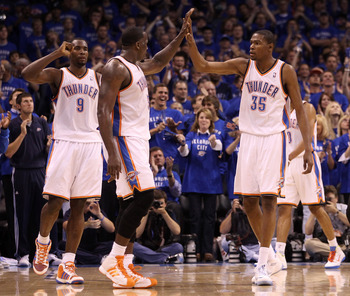 OKLAHOMA CITY, OK - MAY 23:  (R-L) Kevin Durant #35, Kendrick Perkins #5, Serge Ibaka #9 of the Oklahoma City Thunder react in the second quarter while taking on the Dallas Mavericks in Game Four of the Western Conference Finals during the 2011 NBA Playof