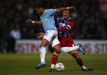 SCUNTHORPE, NORTH LINCS - JANUARY 24:  Robinho of Manchester City goes past Cliff Byrne of Scunthorpe United during the FA Cup sponsored by E.ON Fourth round match between Scunthorpe United and Manchester City at Glanford Park on January 24, 2010 in Scunt