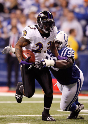 INDIANAPOLIS - JANUARY 16:  Willis McGahee #23 of the Baltimore Ravens runs the ball as Antonio Johnson #99 of the Indianapolis Colts looks to tackle him from behind in the first quarter of the AFC Divisional Playoff Game at Lucas Oli Stadium on January 1