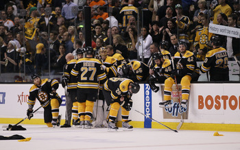 BOSTON - MAY 14:  The  Boston Bruins sit near their bench as the Philadelphia Flyers celebrate the win in Game Seven of the Eastern Conference Semifinals during the 2010 NHL Stanley Cup Playoffs at TD Garden on May 14, 2010 in Boston, Massachusetts. The F