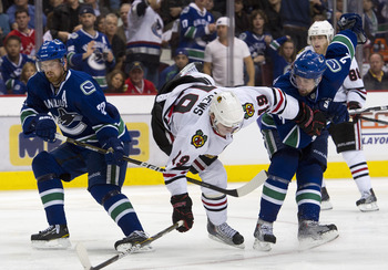 VANCOUVER, CANADA - APRIL 26: Dan Hamhuis #2 of the Vancouver Canucks upends Jonathan Toews #19 of the Chicago Blackhawks during the overtime period in Game Seven of the Western Conference Quarterfinals during the 2011 NHL Stanley Cup Playoffs on April 26