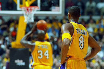 LOS ANGELES - APRIL 10:  Kobe Bryant #8 of the Los Angeles Lakers watches teammate Shaquille O'Neal #34 shoots a free throw during the game against the Sacramento Kings at Staples Center on April 4, 2003 in Los Angeles, California.  The Lakers won 117-104