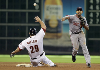 HOUSTON, TX - JULY 20: Second baseman Danny Espinosa #18 of the Washington Nationals turns a double play on Brett Wallace #29 of the Houston Astros in the 10th inning on July 20, 2011 at Minute Maid Park in Houston, Texas. Astros won in the bottom of the