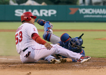 ANAHEIM, CA - JULY 20:  Bobby Abreu #53 of the Los Angeles Angels of Anaheim slides safely past catcher Yorvit Torrealba #8 of the Texas Rangers and scores a run in the first inning at Angel Stadium of Anaheim on July 20, 2011 in Anaheim, California.  (Ph