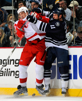 NASHVILLE, TN - APRIL 02:  Valtteri Filppula #51 of the Detroit Red Wings gets checked by David Legwand #11 of the Nashville Predators on April 2, 2011 at the Bridgestone Arena in Nashville, Tennessee.  (Photo by Frederick Breedon/Getty Images)