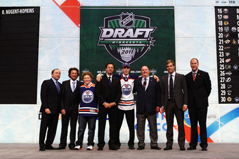 ST PAUL, MN - JUNE 24:  NHL Commissioner Gary Bettman (far left), General Manager Steve Tambellini (4th from Left), first overall pick Ryan Nugent-Hopkins by the Edmonton Oilers, Taylor Hall (2nd from Right) and President of Hockey Operations Kevin Lowe o