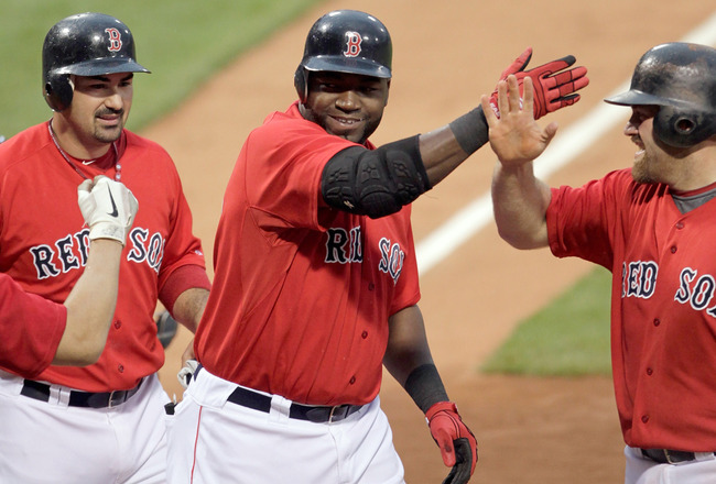 BOSTON, MA - JULY 8:  David Ortiz #34 of the Boston Red Sox celebrates with teammates Kevin Youkilis #20 and Adrian Gonzalez #28 after hitting a three-run home run off of Zach Britton #53 of the Baltimore Orioles in the first inning at Fenway Park on July