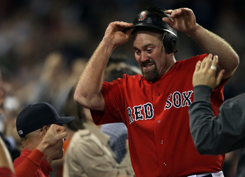 BOSTON, MA - JUNE 03:  Kevin Youkilis #20 of the Boston Red Sox is congratulated after he scored off a hit by teammate Carl Crawford in the seventh inning against the Oakland Athletics on June 3, 2011 at Fenway Park in Boston, Massachusetts.  (Photo by El