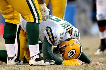 CHICAGO, IL - JANUARY 23:  Quarterback Aaron Rodgers #12 of the Green Bay Packers lays on the turf after getting hit by Julius Peppers #90 of the Chicago Bears in the helmet as Peppers was called for a personal foul in the fourth quarter of the NFC Champi