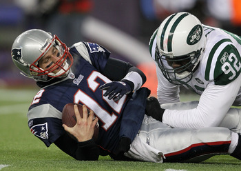 FOXBORO, MA - JANUARY 16:  Quarterback Tom Brady #12 of the New England Patriots is sacked by Shaun Ellis #92 of the New York Jets during their 2011 AFC divisional playoff game at Gillette Stadium on January 16, 2011 in Foxboro, Massachusetts.  (Photo by