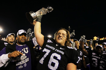 PASADENA, CA - JANUARY 01:  Center Jake Kirkpatrick #76 of the TCU Horned Frogs celebrates with the Rose Bowl Championship Trophy after defeating the Wisconsin Badgers 21-19 in the 97th Rose Bowl game on January 1, 2011 in Pasadena, California.  (Photo by