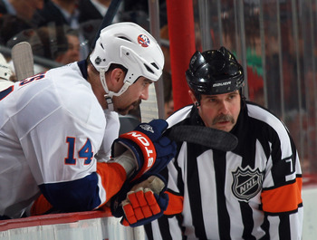NEWARK, NJ - MARCH 30: Referee Bill McCreary #7 and Trevor Gillies #14 of the New York Islanders chat during the first period as the Islanders played against the New Jersey Devils at the Prudential Center on March 30, 2011 in Newark, New Jersey.  (Photo b