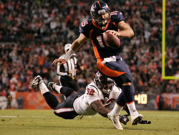 DENVER - DECEMBER 26:  Quarterback Tim Tebow #15 of the Denver Broncos escapes a diving effort by defensive tackle Earl Mitchell #92 of the Houston Texans on his way to scoring the game-winning touchdown in the fourth quarter at INVESCO Field at Mile High