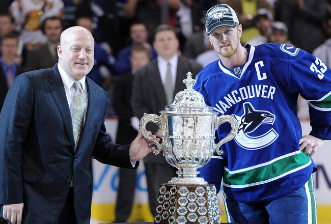 VANCOUVER, BC - MAY 24:  NHL Deputy Commissioner Bill Daly and Captain Henrik Sedin #33 of the Vancouver Canucks pose with the Clarence Campbell Bowl after the Vancouver Canucks defeated the San Jose Sharks 3-2 in double-overtime in Game Five to win the W
