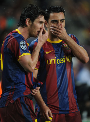 BARCELONA, SPAIN - MAY 03:  Lionel Messi (L) of Barcelona lines up a free kick with his teammate Xavi Hernandez during the UEFA Champions League Semi Final second leg match between Barcelona and Real Madrid at the Camp Nou stadium on May 3, 2011 in Barcel